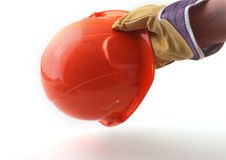 Worker in protective gloves holds an orange hard hat in his hand. Safety helmet. Stock Photos