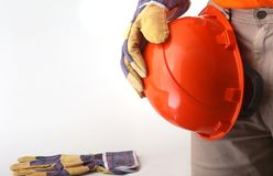 Worker in protective gloves holds an orange hard hat in his hand. Safety helmet. Royalty Free Stock Images