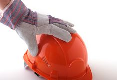 Worker in protective gloves holds an orange hard hat in his hand. Safety helmet. Stock Photo
