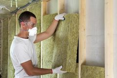 Worker in protective goggles and respirator insulating rock wool stock photography