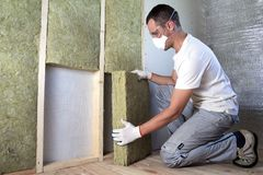 Worker in protective goggles and respirator insulating rock wool insulation in wooden frame for future house walls for cold royalty free stock photography