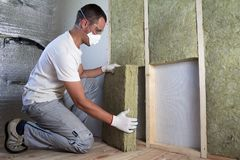 Worker in protective goggles and respirator insulating rock wool stock image