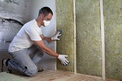 Worker in protective goggles and respirator insulating rock wool royalty free stock photo