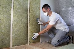 Worker in protective goggles and respirator insulating rock wool stock photo