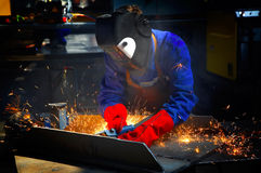 Worker with protective mask and gloves grinding/we. Lding metal and sparks spreading Royalty Free Stock Photography