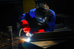 Worker with protective mask and gloves grinding/we. Lding metal and sparks spreading stock photo