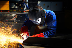 Worker with protective mask and gloves grinding. /welding metal and sparks spreading Stock Photo