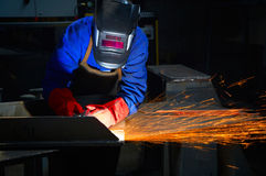 Worker with protective mask and gloves grinding. /welding metal and sparks spreading Royalty Free Stock Photos