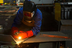 Worker with protective mask and gloves grinding. /welding metal and sparks spreading stock photos