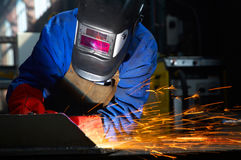 Worker with protective mask and gloves grinding/we. Lding metal and sparks spreading Stock Images