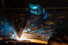 Worker with protective mask welding metal. In automotive assembly factory Royalty Free Stock Image