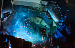 Worker with protective mask welding metal. In the automotive parts industry Stock Images