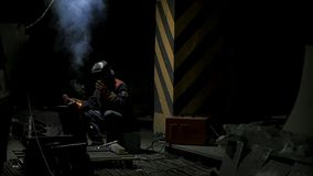 Worker with protective mask welding metal.welding in black background in slow motion. Man with protective mask welding. Metal in dark contrast background in Stock Images