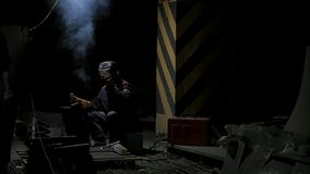 Worker with protective mask welding metal.welding in black background in slow motion. Man with protective mask welding. Metal in dark contrast background in Stock Image