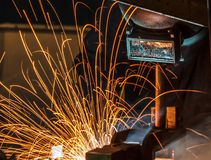 Worker with protective mask welding metal, blur. Welder and bright sparks. Construction and manufacturing Stock Image