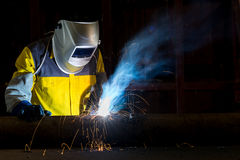 Worker with protective mask welding metal in factory Royalty Free Stock Photos