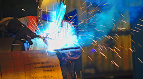 Worker with protective mask welding metal. And sparks Royalty Free Stock Image