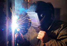Worker with protective mask welding metal. And sparks Stock Photos