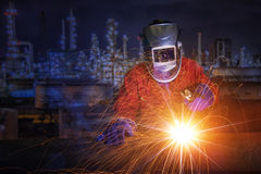Worker with protective mask welding metal and sparks. In oil refinary plant Stock Photography