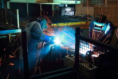 Worker with protective mask welding metal. The team work Stock Photo