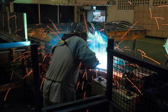 Worker with protective mask welding metal. The team work Stock Image