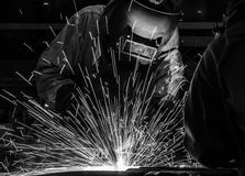 Worker with protective mask welding metal. Welder Industrial automotive part in factory Royalty Free Stock Photos