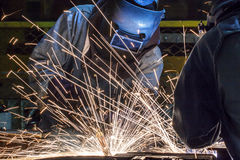 Worker with protective mask welding metal. Welder Industrial automotive part in factory Royalty Free Stock Images