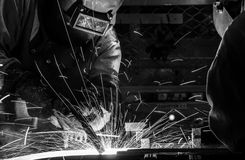 Worker with protective mask welding metal. Welder Industrial automotive part in factory Stock Photography