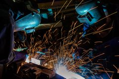 Worker with protective mask welding metal. In automotive assembly factory Royalty Free Stock Photo