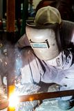 Worker with protective mask welding metal. Workers with protective metal mask welded inside the factory Stock Image