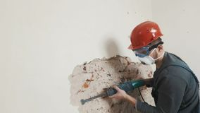 Worker in protective suit demolishes plaster wall. Dirty, hard work. Personal protective equipment. Helmet, respirator