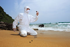 Worker in a protective suit examining pollution Stock Photos