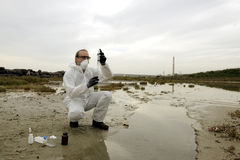 Worker in a protective suit examining pollution Royalty Free Stock Photo