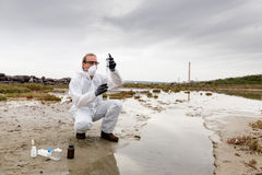 Worker in a protective suit examining pollution. In the water at the industry Stock Photos