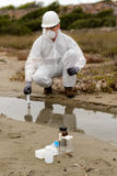 Worker in a protective suit examining pollution. In the water at the industry Stock Photography