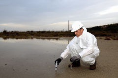 Worker in a protective suit examining pollution. Stock Image