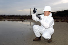 Worker in a protective suit examining pollution. Royalty Free Stock Photos