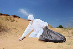 Worker in protective suit holding a waste bag and collecting sam Royalty Free Stock Images