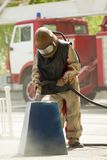 Worker in a protective suit spraying sand Stock Photos