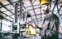 Worker in protective uniform in front of forklift Royalty Free Stock Photo