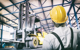 Worker in protective uniform in front of forklift Royalty Free Stock Photography