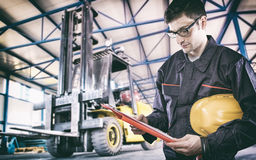 Worker in protective uniform in front of forklift Stock Photo