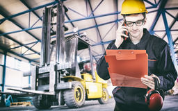 Worker in protective uniform in front of forklift Royalty Free Stock Image