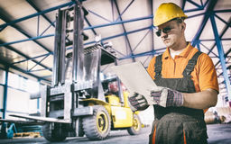 Worker in protective uniform in front of forklift. Worker in protective uniform in production hall in front of forklift - toned image, retro film filtered in Royalty Free Stock Photography