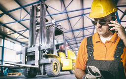Worker in protective uniform in front of forklift. Worker in protective uniform in production hall in front of forklift - toned image, retro film filtered in Stock Photography