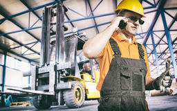 Worker in protective uniform in front of forklift. Worker in protective uniform in production hall in front of forklift - toned image, retro film filtered in Stock Image