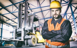 Worker in protective uniform in front of forklift Stock Image