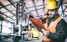 Worker in protective uniform in front of forklift Royalty Free Stock Photos
