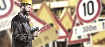 Worker in protective uniform in front of road signs. Worker in protective uniform and protective helmet in front of road signs - toned image, retro film filtered Royalty Free Stock Photography