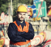 Worker in protective uniform in front of road signs. Worker in protective uniform and protective helmet in front of road signs - toned image, retro film filtered Stock Image
